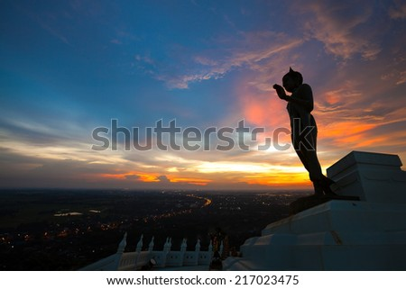 Standing Buddha image silhouette on sunset sky    - stock photo