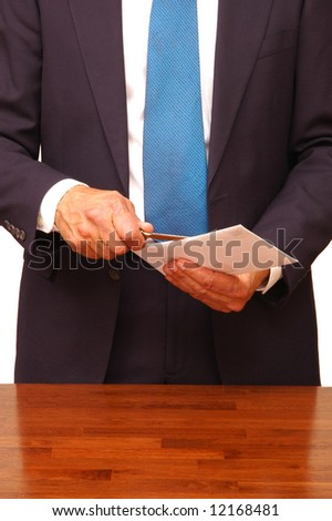 Standing Businessman Opening an Envelope at Desk