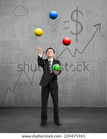 standing businessman playing colorful balls on concrete floor with doodles wall - stock photo