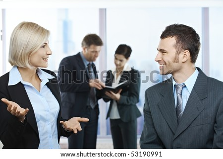 Standing businesspeople talking in office smiling at each other, coworkers looking at documents in background. - stock photo