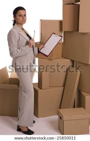 standing businesswoman keeping glasses and clipboard, cardboard boxes in background