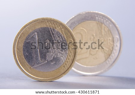 Standing coins one euro and two euro isolated on the gray background - stock photo