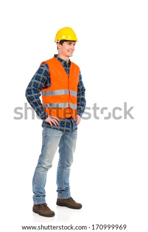 Standing construction worker in yellow helmet and orange waistcoat. Full length studio shot isolated on white.