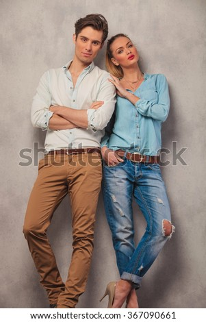 standing couple posing in studio background, man with hands crossed while woman with hand in pocket touch man's shoulder - stock photo