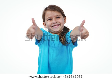 Standing girl showing thumbs to camera on white screen - stock photo