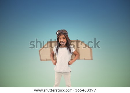 Standing girl with fake wings pretending to be pilot against blue sky - stock photo