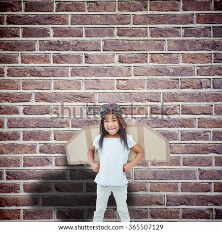Standing girl with fake wings pretending to be pilot against red brick wall - stock photo