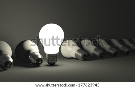 Standing glowing light bulb in row of lying switched off ones on dark gray textured background