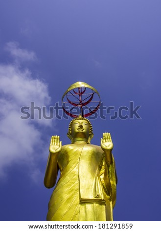 standing golden buddha statue and blue sky - stock photo