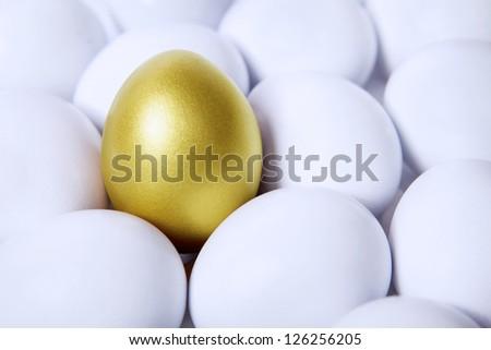 Standing golden egg in between white eggs - stock photo