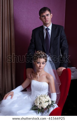 Standing groom behind sitting bride with bouquet of roses in stylish interior
