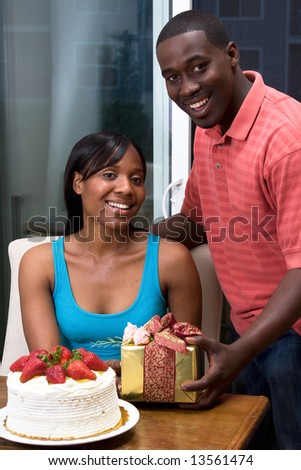 Standing handsome man giving an attractive woman, who is sitting by a cake, a gift.  Vertical framed shot with both people smiling and looking at the camera.