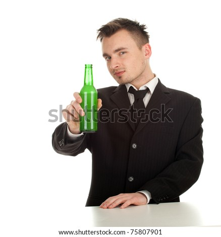 standing happy young man in black suit with bottle of beer - stock photo
