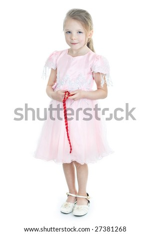 Standing little girl in pink dress with red glass beads in hands