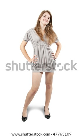 Standing long-haired teen girl in grey dress. Isolated on white