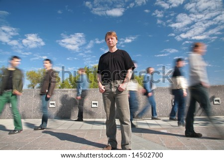 standing man among moving pedestrians