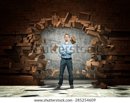 standing man and brick wall explosion - stock photo