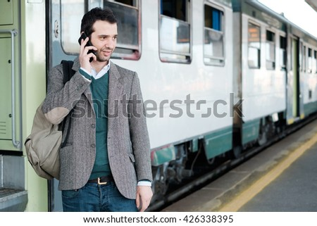 standing man calling on the phone waiting for the train in a train station platform - stock photo