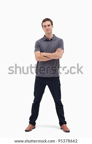 Standing man crossing his arms and his legs apart against white background - stock photo