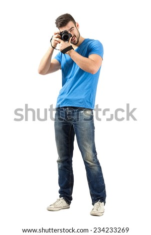 Standing man focusing lens of dslr looking at camera. Full body length portrait isolated over white background.
