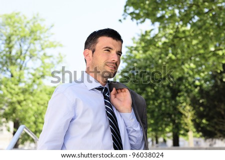 standing man waiting outdoor in a park - stock photo