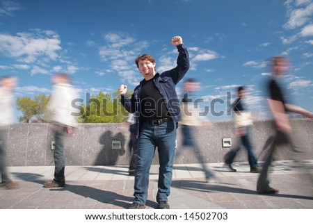 standing man with the lifted hands among moving pedestrians - stock photo
