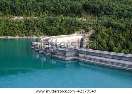 Standing 103 metres above the Ain River, the curved vault of the Vouglans dam is situated on the first Jura plateau. - stock photo