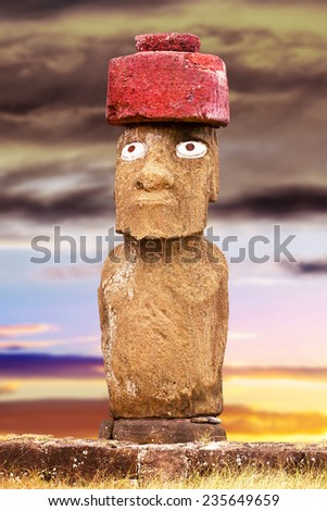 Standing moai with red stone hat and eyes in Easter Island, Chile - stock photo