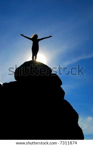 Standing on cliff top with arms outstretched - stock photo