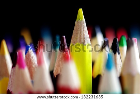 Standing out from the crowd concept with colored pencils - stock photo
