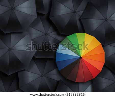 Standing out from the crowd, high angle view of colorful  umbrella over many black ones - stock photo