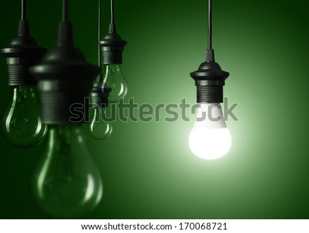 Standing out of the crowd or great idea concept, glowing light bulb over green background - stock photo