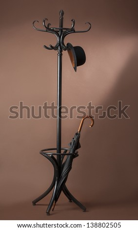standing peg with umbrella and hat - stock photo