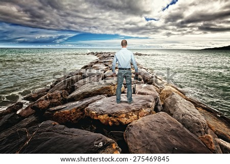 standing photographer on sea rock reef - stock photo