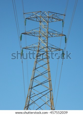 Standing power tower with power lines and insulators, against the blue sky