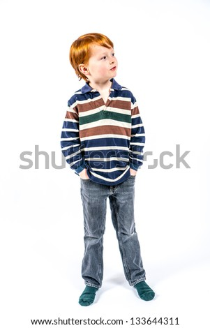 standing red-haired six years old boy on a white background, dressed in striped shirt and jeans