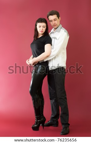 Standing Sad couple on red burgundy background - stock photo