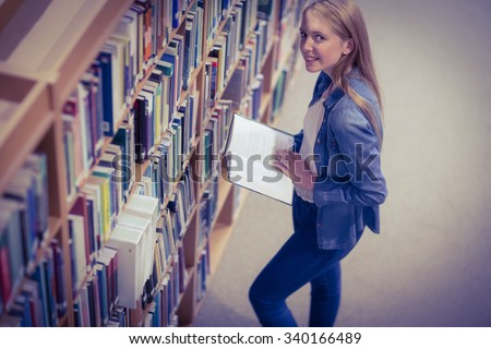 Standing student reading book in library at the university - stock photo