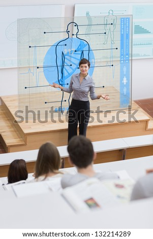 Standing teacher in front of futuristic interface asking a question to students - stock photo