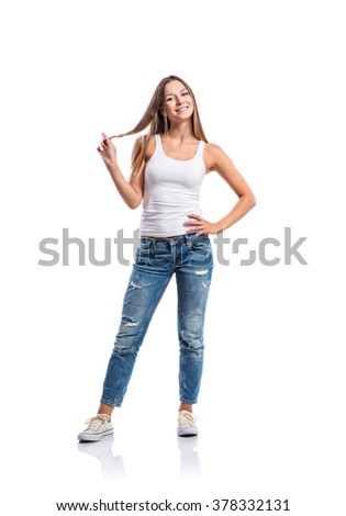 Standing teenage girl in jeans, tight singlet and sneakers, twirling her hair, young woman, isolated on white background - stock photo