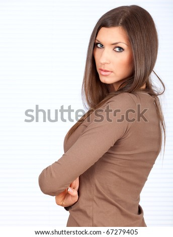 standing thoughtful beautiful young woman with crossed arms - stock photo