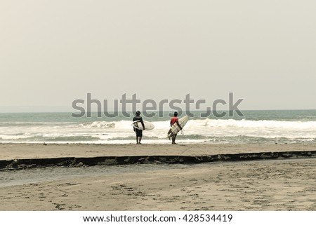 Standing two male surfers on the beach