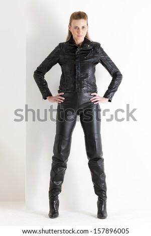 standing woman wearing black clothes and black boots - stock photo