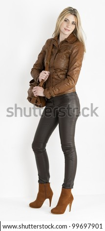standing woman wearing brown clothes and fashionable brown shoes with a handbag