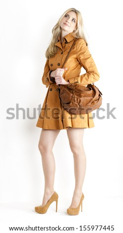 standing woman wearing brown coat and pumps with a handbag