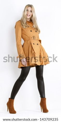 standing woman wearing coat and fashionable brown shoes