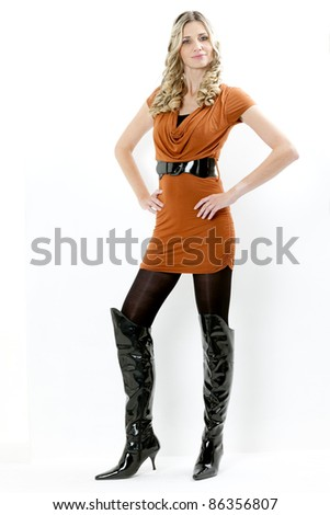 standing woman wearing dress and fashionable black boots