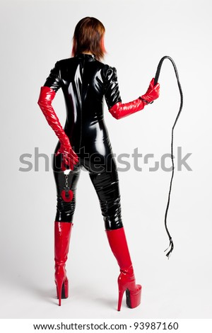 standing woman wearing extravagant clothes holding a whip and handcuffs - stock photo