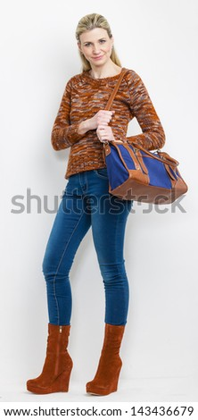 standing woman wearing fashionable platform brown shoes with a handbag - stock photo
