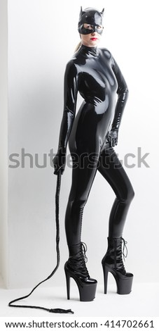 standing woman wearing latex clothes with a whip - stock photo